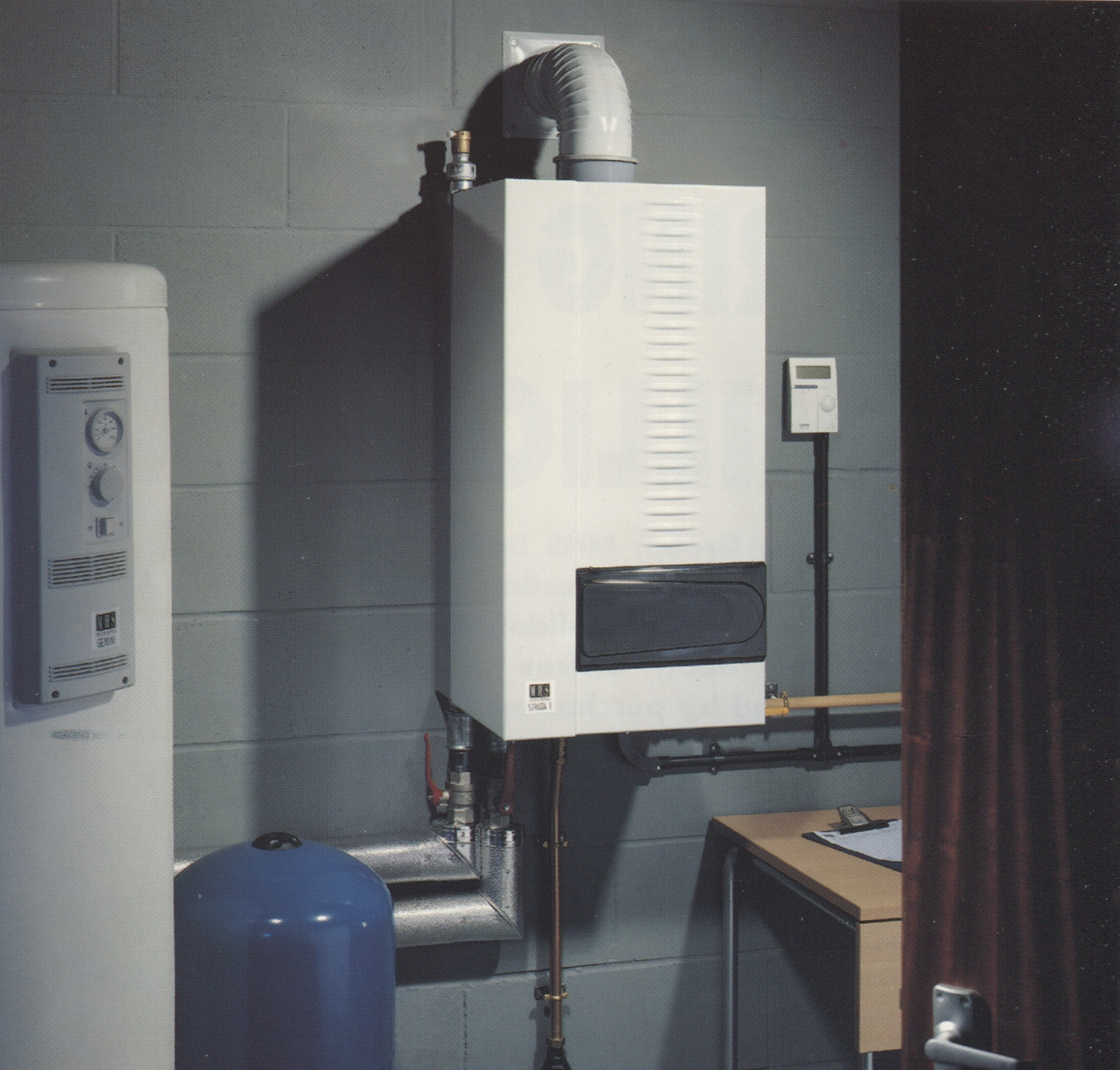 Modern wall hung white commercial boiler on a grey wall