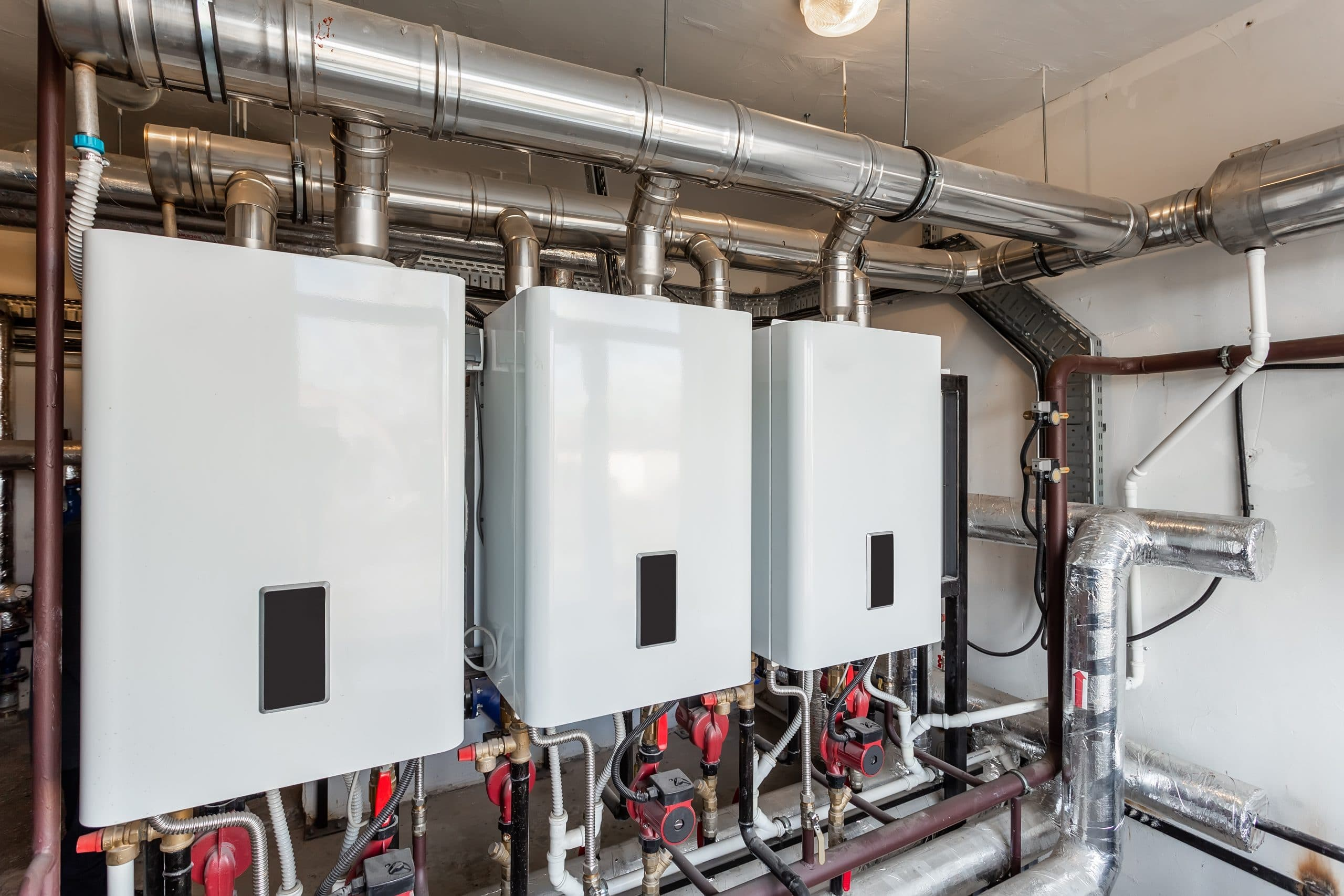 Row of three white wall hung commercial boilers